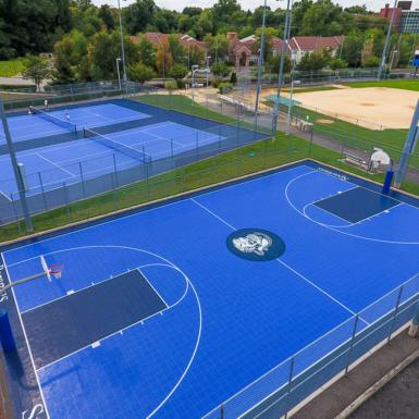 Esta es una cancha de baloncesto en un parque público. El piso de la cancha es BounceBack al aire libre. Los colores son azul brillante y azul oscuro.