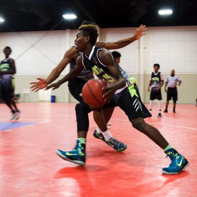 Esta foto es un juego de baloncesto en una cancha roja. Un jugador bota la pelota y el otro jugador intenta bloquearlo.