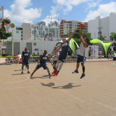 En Dew NBA 3X Miami varios jugadores se elevan en un salto y procuran por el balón en un campo construido al aire libre.