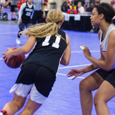 Una jugadora ataca, con balón dominado, mientras una contrincante, bien plantada,defiende.