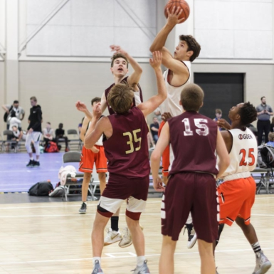 Un niño toma un tiro durante un juego de baloncesto AAU. Dos equipos juegan en un cancha SnapSports.