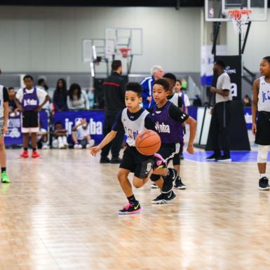 Los niños practican en un evento de Jr NBA. Este evento fue durante la Semana de All-Star de la NBA. El piso de la cancha es Revolution.