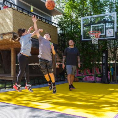 La familia de Nick Rimando juega baloncesto en la cancha de su patio trasero. La cancha es gris con una llave amarilla y líneas moradas. La cancha es Revolution al aire libre.
