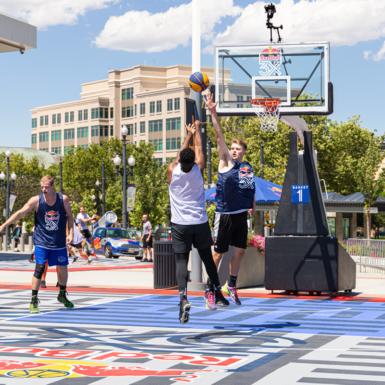 Un tiro esta bloqueado en un Juego en un torneo baloncesto de Red Bull. La cancha es  Revolution al aire libre. Dos equipos está juegano.
