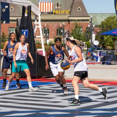 Esta es una fotografía de un torneo de baloncesto femenino de Red Bull en Salt Lake City. Una mujer bota el baloncesto mientras otra se defiende contra ella.