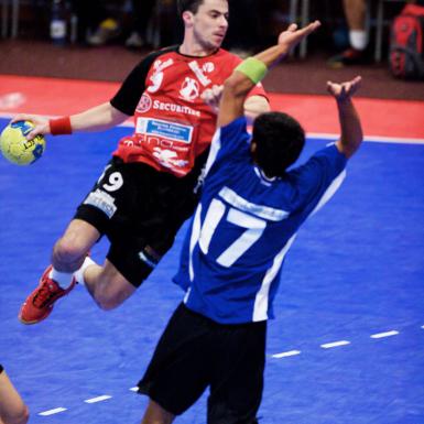 Jugadores de handball en cancha azul y roja