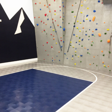 Cancha de baloncesto en casa con muro de escalada