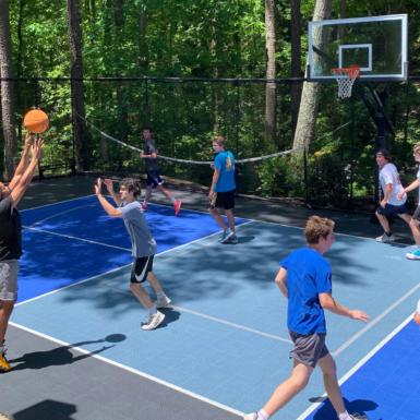 Niños juegan baloncesto en cancha de usos múltiples