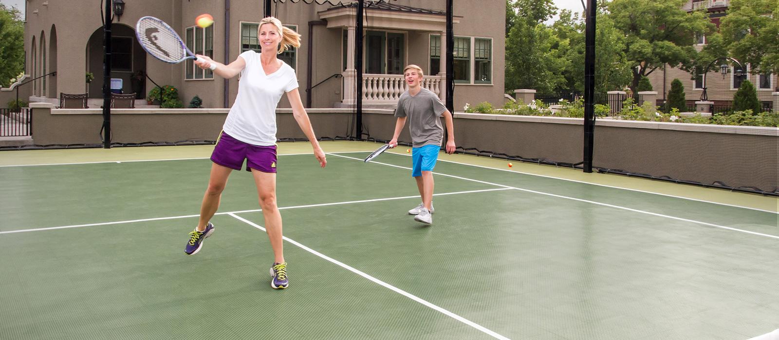 Una mujer y su hijo juegan tenis en una de las canchas de tenis de SnapSports.
